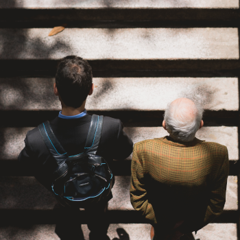 Older and younger worker on subway steps